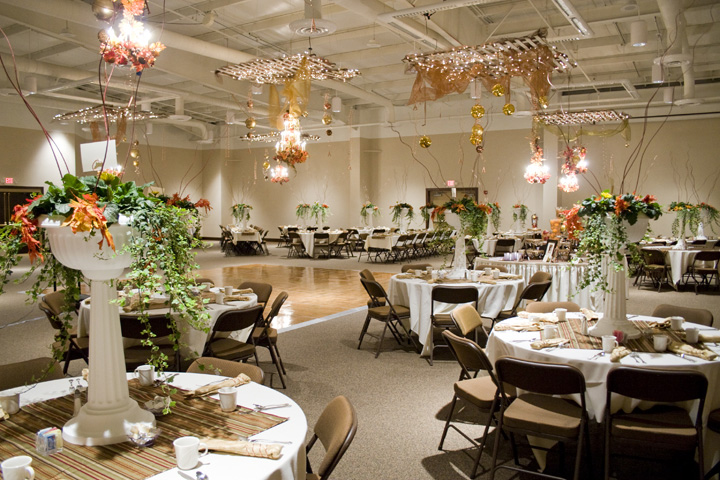 A wedding venue with a dance floor and tables decorated and ready for guests.