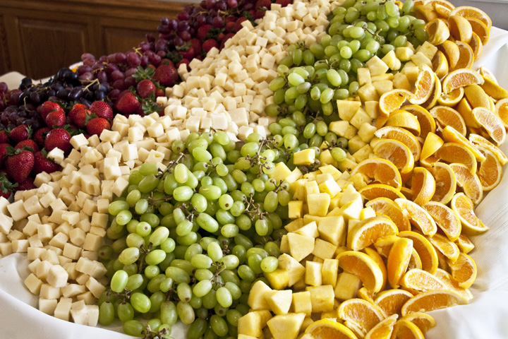 A table full of fresh fruit and cheeses on a Blue Gate Catering buffet.