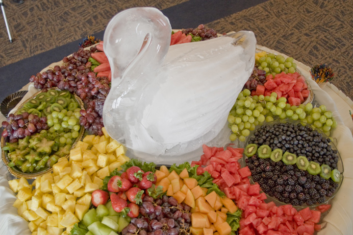 A large display of fruit and an ice sculpture of a swan