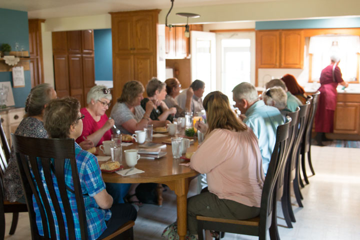 A group samples some sweet rolls prepared by a local Amish homemaker