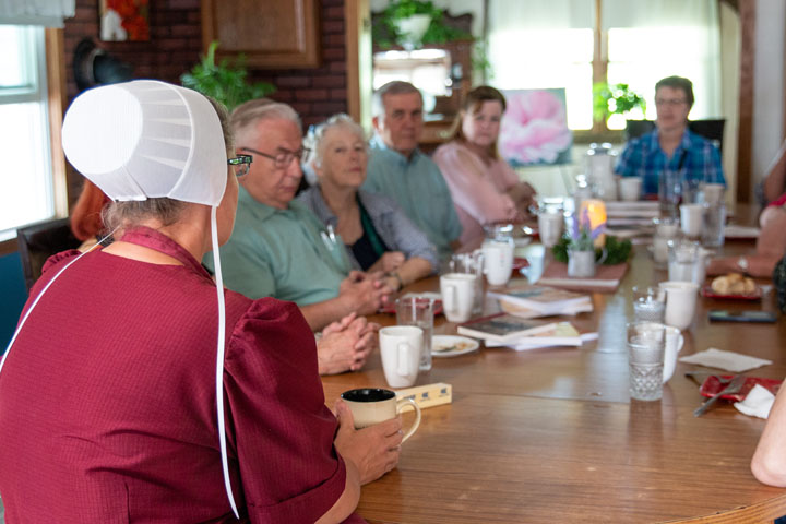 A group talks to a local Amish homemaker around her family table
